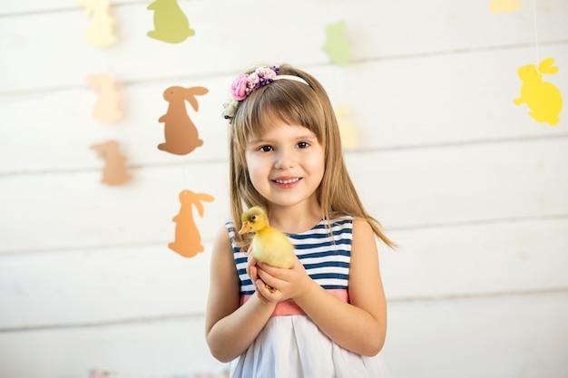 Menina feliz com flores na cabeça, segurando um lindo patinho de páscoa fofo.