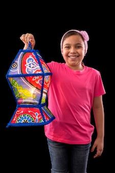 Menina feliz com grande lanterna do ramadã em fundo preto