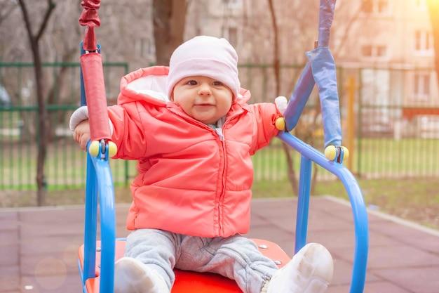 Menina feliz com jaqueta rosa e chapéu branco balançando no balanço dia ensolarado de primavera