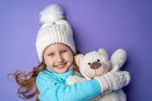 Menina feliz com luvas segurando um ursinho de pelúcia