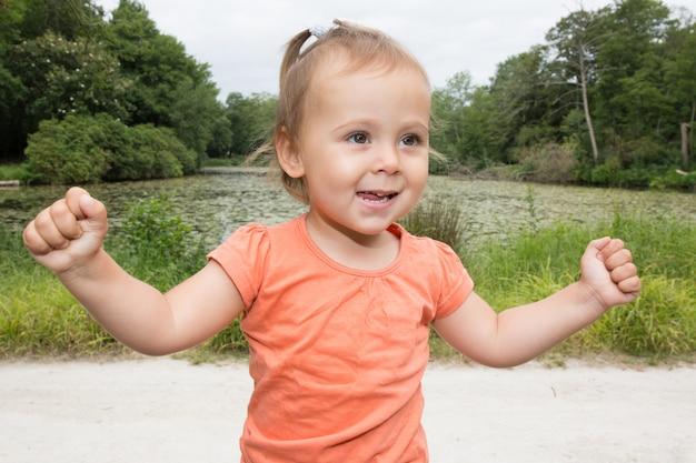 Menina feliz com mãos levantadas no parque de verão