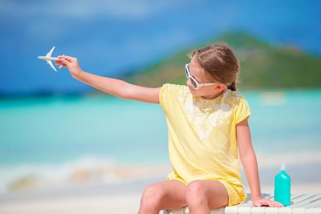 Menina feliz com o avião do brinquedo nas mãos na praia arenosa branca.