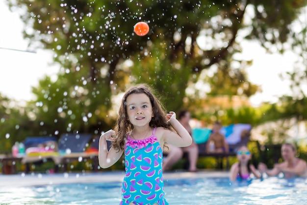 Menina feliz com o cabelo para baixo em um maiô brilhante jogando bola na piscina em um dia ensolarado de verão