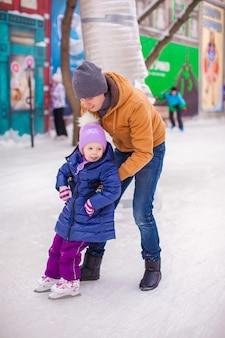 Menina feliz com o jovem pai se divertir na pista de patinação