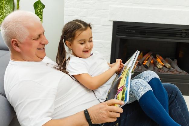 Menina feliz com o livro de história de leitura de avô em casa