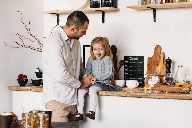 Menina feliz com o pai na cozinha em casa