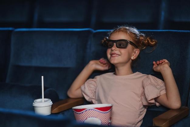Menina feliz com óculos 3d e pipoca no cinema, assistindo o filme.