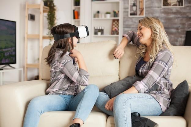Menina feliz com óculos de realidade virtual, jogando jogos. mãe linda.