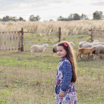 Menina feliz com ovelhas na fazenda