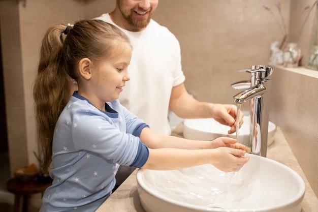 Menina feliz com pijama azul, lavando as mãos na pia pela manhã, no fundo do pai, parado por perto no banheiro