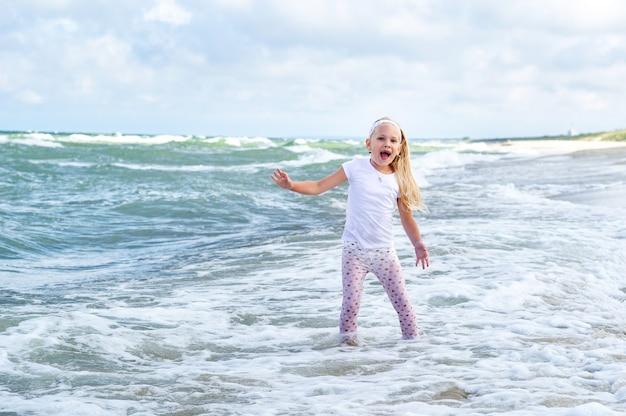 Menina feliz com roupas na praia do mar báltico, no espeto da curlândia, na lituânia.