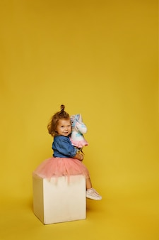 Menina feliz com saia rosa e jaqueta jeans com um cavalo de brinquedo na parede amarela