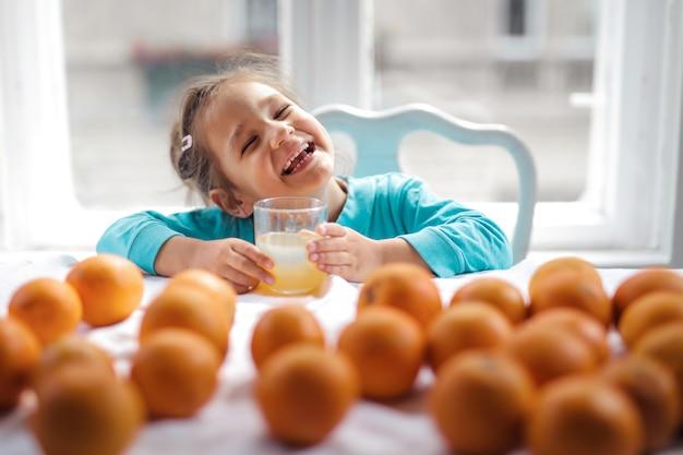 Menina feliz com suco de laranja