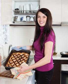 Menina feliz com torta de peixe cozida
