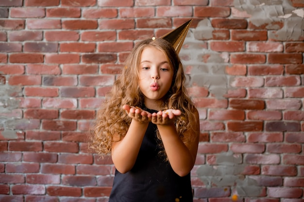 Menina feliz com um boné de aniversário explodindo nas palmas das mãos de confete