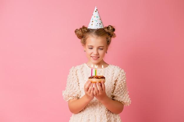 Menina feliz com um boné de aniversário faz um pedido e apaga velas em um bolo.