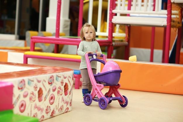 Menina feliz com um carrinho em um centro de entretenimento infantil