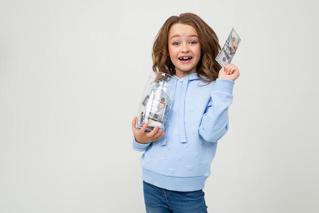Menina feliz com um frasco de vidro e dinheiro em um branco com espaço da cópia. finança