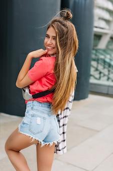 Menina feliz com um penteado moderno em shorts jeans dançando com um lindo sorriso e olhando por cima do ombro