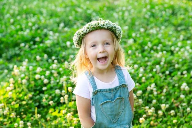 Menina feliz com uma coroa de trevo na cabeça dela sorrindo ao ar livre