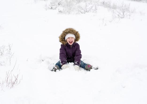 Menina feliz com uma jaqueta roxa de inverno sentada na neve e rindo com a boca aberta