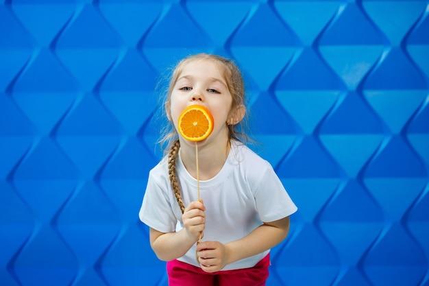 Menina feliz com uma laranja na mão, olha para a câmera vestida de camiseta branca, isolada em um fundo azul, copie o espaço,