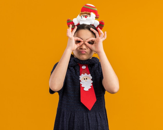 Menina feliz com vestido de tricô usando gravata vermelha com aro de natal engraçado na cabeça olhando por entre os dedos fazendo gesto binocular