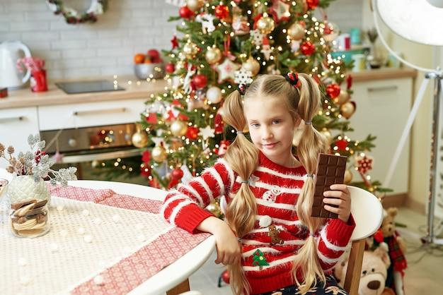 Menina feliz comendo chocolate na mesa na cozinha doméstica com árvore de natal