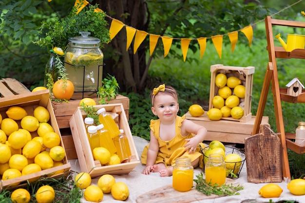 Menina feliz comendo limões e bebendo limonada ao ar livre no verão