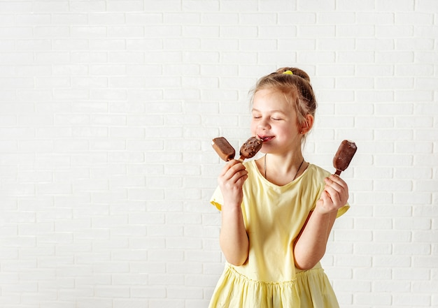 Menina feliz comendo sorvete de chocolate picolé no horário de verão