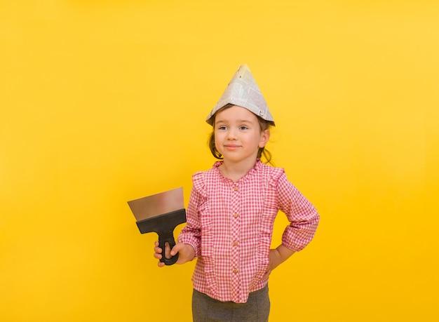 Menina feliz construção com uma espátula e jornal de papel em um amarelo isolado
