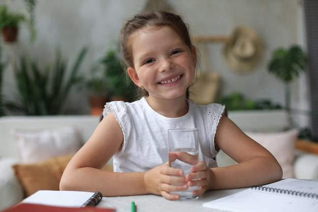Menina feliz contém água mineral cristalina em vidro, criança pequena recomenda uma dose diária de água limpa.