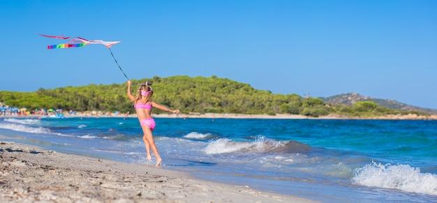 Menina feliz correndo com pipa na praia tropical