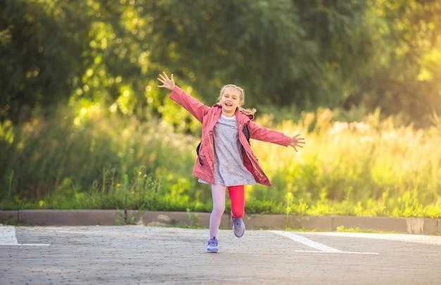 Menina feliz correndo de braços abertos no estacionamento depois da escola