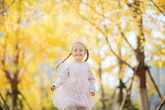 Menina feliz correndo no parque outonal