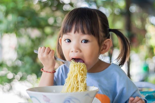 Menina feliz criança asiática gosta de comer macarrão sozinha.