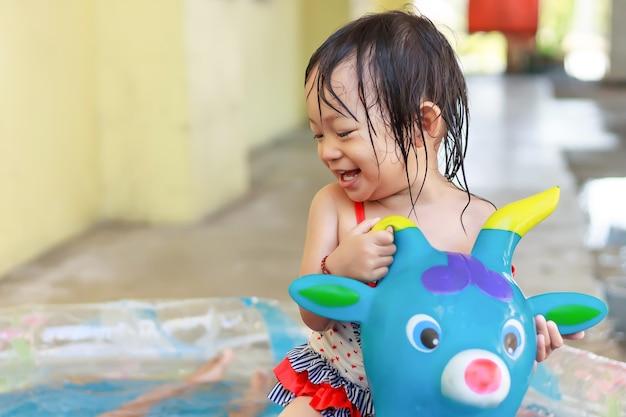 Menina feliz criança asiática nadando e jogando água na piscina azul ela sorri e ri