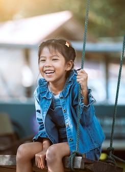 Menina feliz criança asiática se divertindo para jogar em balanços de madeira no parque infantil no parque