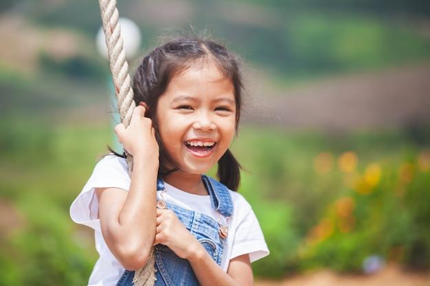Menina feliz criança asiática se divertindo para jogar em balanços de madeira no parque infantil