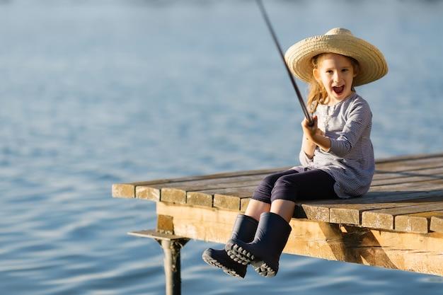 Menina feliz criança bonitinha em botas de borracha, pesca de cais de madeira em um lago.