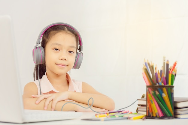 Menina feliz criança com fones de ouvido e olhando para a câmera