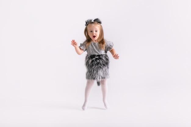 Menina feliz criança emocional engraçada na fantasia de lobo bonito em fundo de cor branca.
