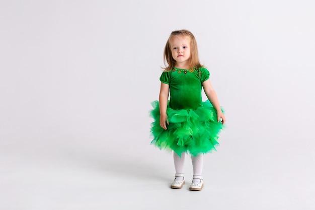 Menina feliz criança emocional engraçada no lindo traje de véspera de natal verde em fundo de cor branca.