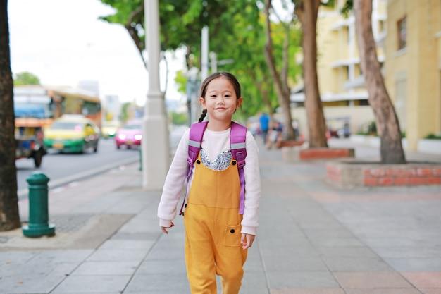 Menina feliz da criança asiática que anda com o schoolbag do ombro do estudante.