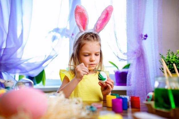 Menina feliz da páscoa nas orelhas do coelho que pintam ovos, criança pequena em casa. feriado de primavera