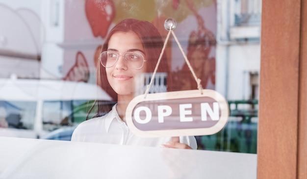 Menina feliz da pequena empresa mudando de posição para abrir a placa na janela sorrindo olhando para fora