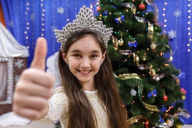 Menina feliz de 10 anos apareça polegar para cima, assine ok