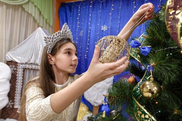 Menina feliz de 10 anos decorando a árvore de natal em casa interior.