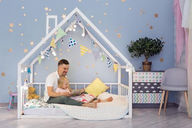 Menina feliz de 3 anos e seu pai bonito, lendo um livro enquanto está sentado na cama de casa bonita