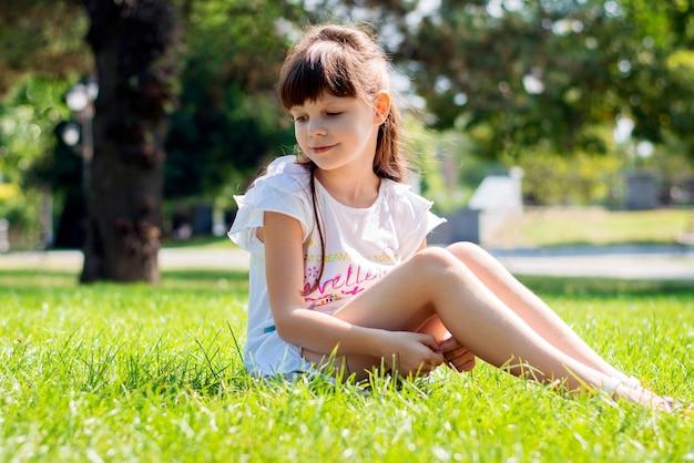 Menina feliz de 8 anos em um vestido branco e longos cabelos escuros sentada em um gramado verde